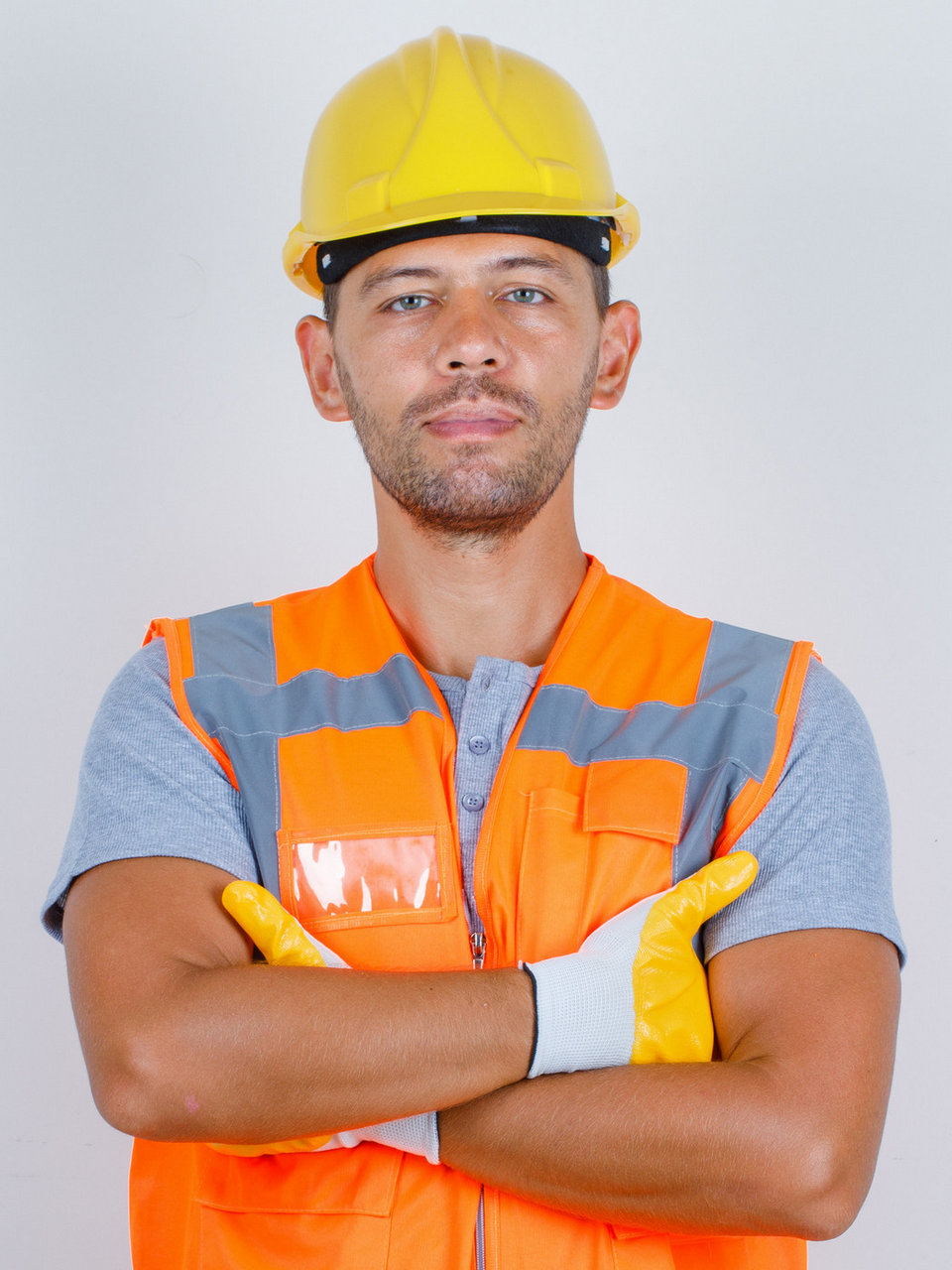 Male builder in uniform standing with crossed arms and looking confident , front view.